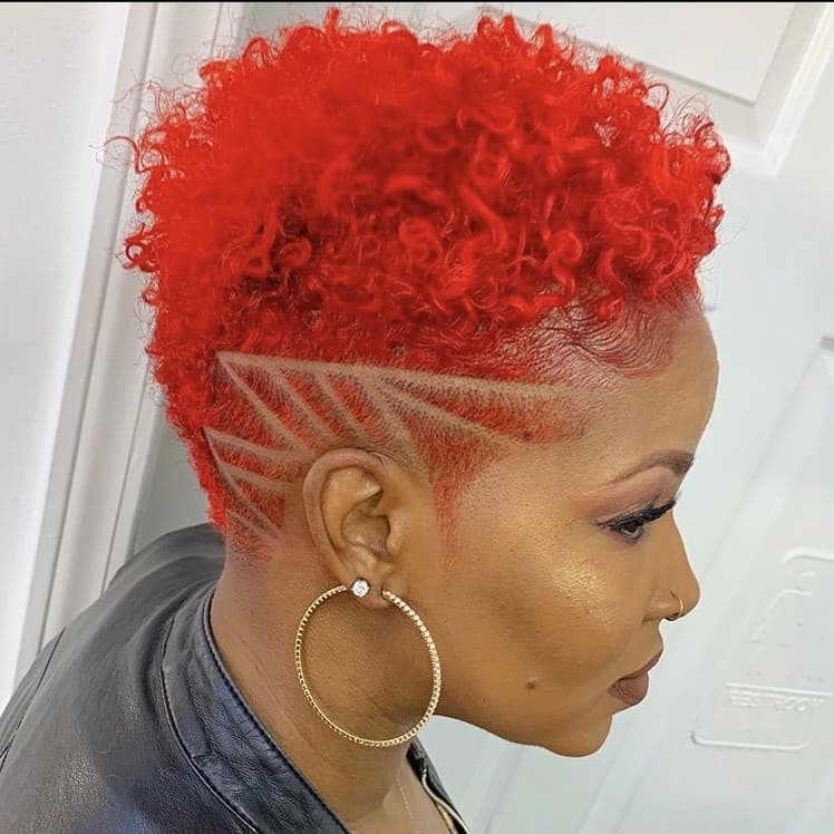 Curly tapered haircut with red hair dye